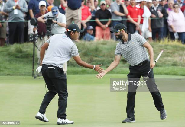 Hideki Matsuyama of Japan and the International Team and Adam Hadwin of Canada and the International Team celebrate during Friday fourball matches of...