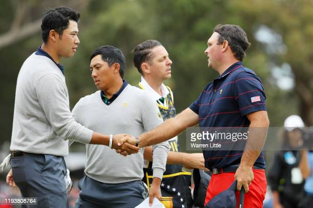 Hideki Matsuyama of Japan and the International team shakes hands with Patrick Reed of the United States team after he and CT Pan of Taiwan and the...