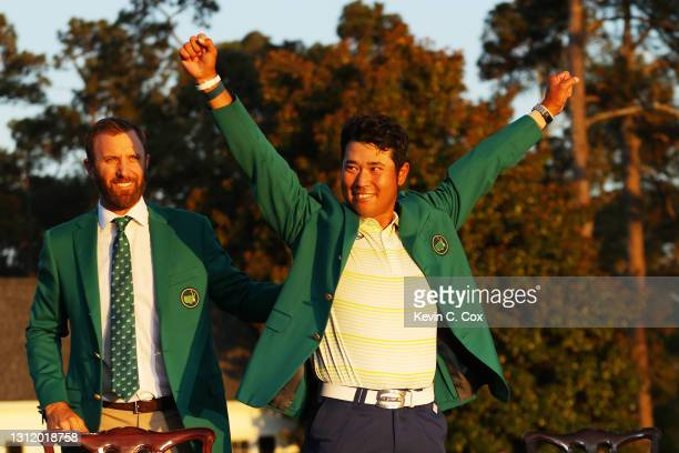 Hideki Matsuyama of Japan celebrates as 2020 Masters champion Dustin Johnson of the United States places the green jacket on him after winning the...