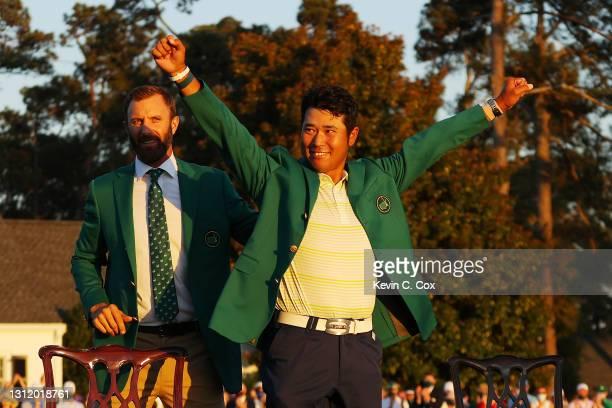 Hideki Matsuyama of Japan celebrates as 2020 Masters champion Dustin Johnson of the United States places the green jacket on him after winning the...