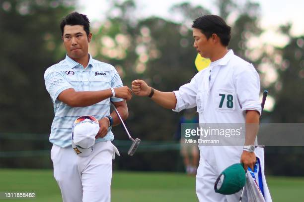 Hideki Matsuyama of Japan celebrates with his caddie Shota Hayafuji after finishing on the 18th green during the third round of the Masters at...