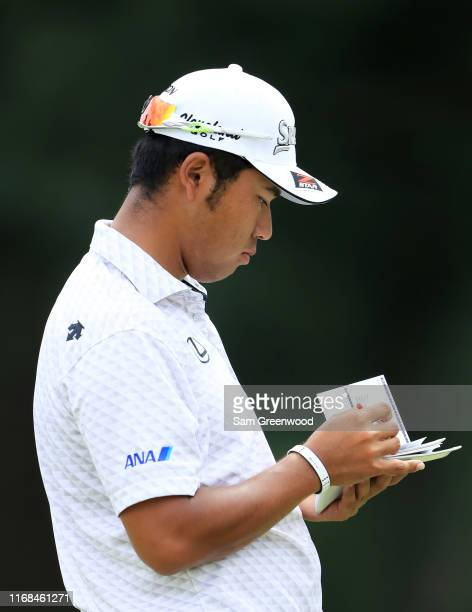 Hideki Matsuyama of Japan checks his yardage book during the second round of the BMW Championship at Medinah Country Club No 3 on August 16 2019 in...