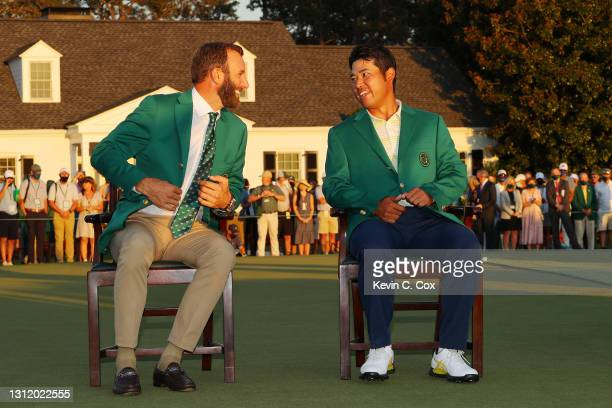 Hideki Matsuyama of Japan laughs with 2020 Masters champion Dustin Johnson of the United States during the Green Jacket Ceremony after Matsuyama won...