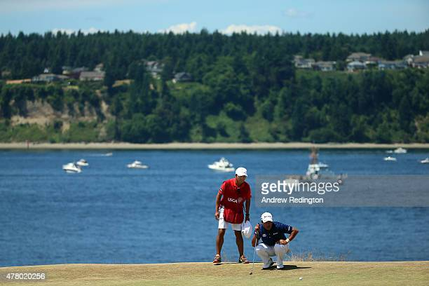 Hideki Matsuyama of Japan lines up his putt with caddie Daisuke Shindo on the second green during the final round of the 115th US Open Championship...