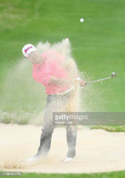 Hideki Matsuyama of Japan plays a shot from a bunker on the 16th hole in his match against Dustin Johnson of the United States during the third round...