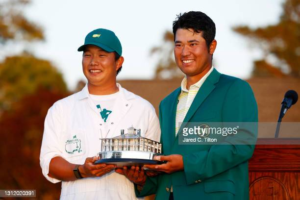 Hideki Matsuyama of Japan poses with his caddie, Shota Hayafuji, and the Masters Trophy during the Green Jacket Ceremony after winning the Masters at...