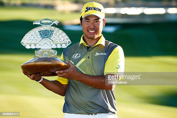 Hideki Matsuyama of Japan poses with the winners trophy on the 18th hole during the final round of the Waste Management Phoenix Open at TPC...