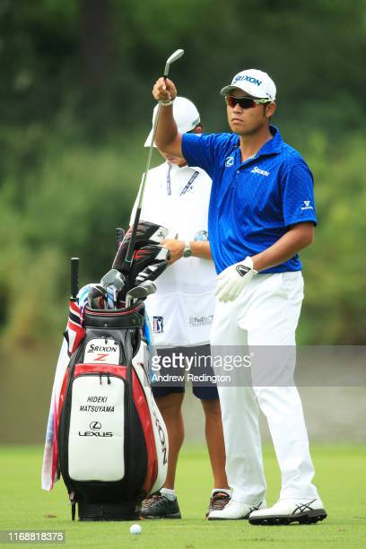 Hideki Matsuyama of Japan pulls a club from his bag as he prepares to play a shot on the 14th hole during the final round of the BMW Championship at...
