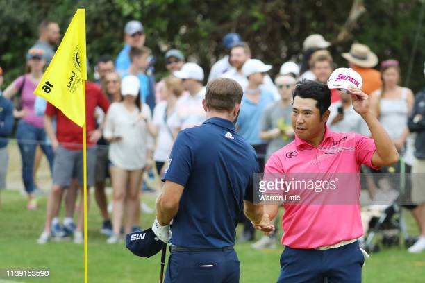 Hideki Matsuyama of Japan shakes hands with Dustin Johnson of the United States after defeating him 32 during the third round of the World Golf...