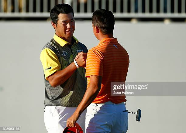 Hideki Matsuyama of Japan shakes hands with Rickie Fowler after putting in to win on the fourth playoff hole on the 17th hole during the final round...