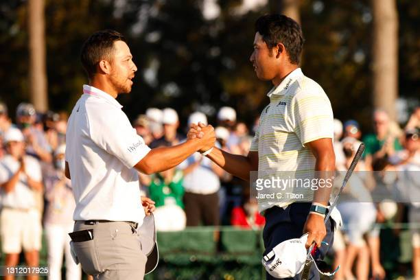 Hideki Matsuyama of Japan shakes hands with Xander Schauffele of the United States on the 18th green after winning the Masters at Augusta National...