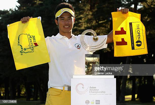 Hideki Matsuyama of Japan stands with the winner's trophy along with the flag of The British Open and Masters Tournament the final round of the 2010...