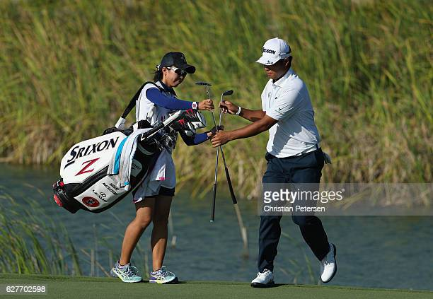 Hideki Matsuyama of Japan swaps clubs with caddie Mei Inui after chipping to the 12th green during the final round of the Hero World Challenge at...