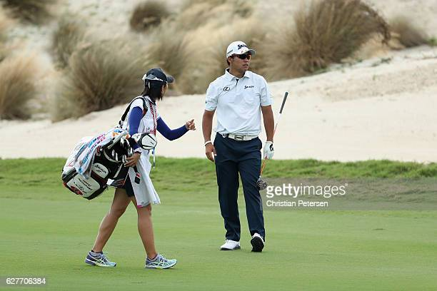 Hideki Matsuyama of Japan talks with caddie Mei Inui on the third hole during the final round of the Hero World Challenge at Albany The Bahamas on...
