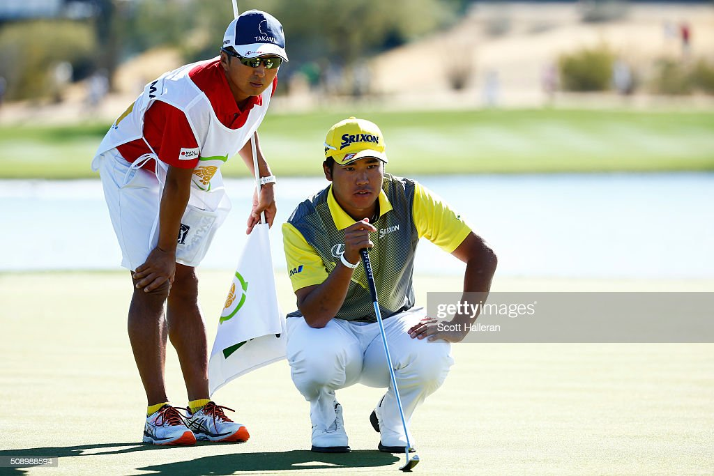 Hideki Matsuyama of Japan talks with his caddie Daisuke Shindo as he prepares to putt during the final round of the Waste Management Phoenix Open at TPC Scottsdale on February 7, 2016 in Scottsdale, Arizona.