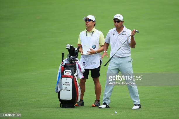 Hideki Matsuyama of Japan talks with his caddie on the third hole during the second round of the BMW Championship at Medinah Country Club No 3 on...
