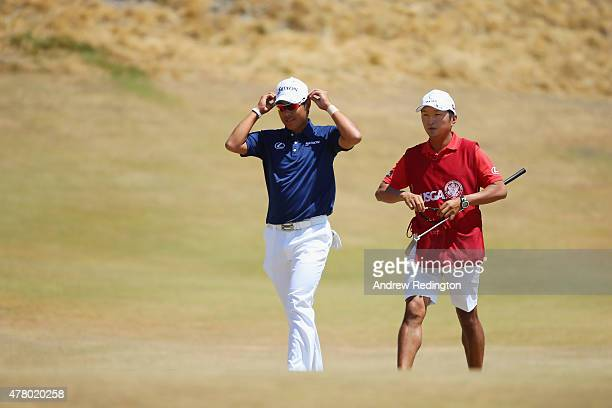 Hideki Matsuyama of Japan walks across the first green with caddie Daisuke Shindo during the final round of the 115th US Open Championship at...