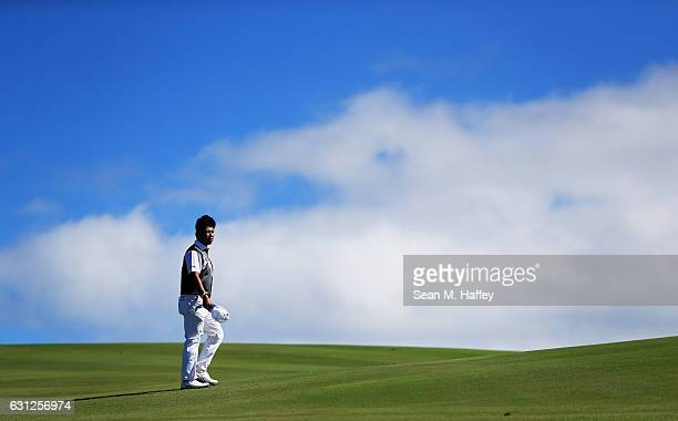 Hideki Matsuyama of Japan walks on the 12th hole during the final round of the SBS Tournament of Champions at the Plantation Course at Kapalua Golf...