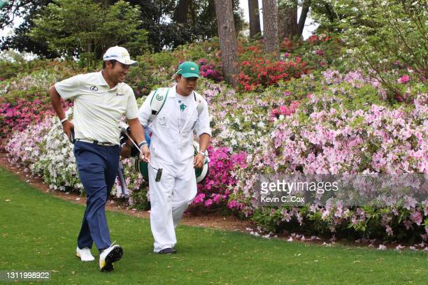 Hideki Matsuyama of Japan walks to the sixth green with his caddie, Shota Hayafuji, during the final round of the Masters at Augusta National Golf...