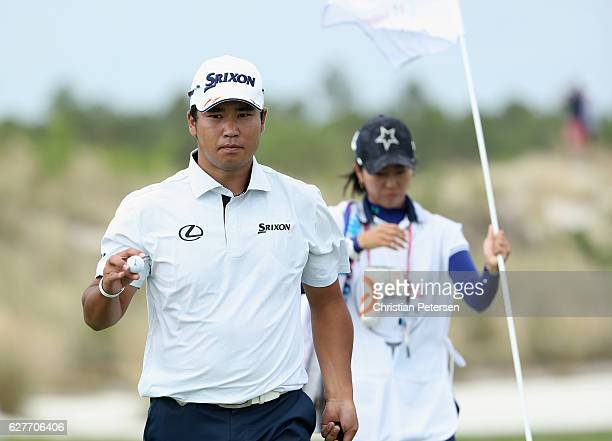 Hideki Matsuyama of Japan waves alongside caddie Mei Inui on the first hole during the final round of the Hero World Challenge at Albany The Bahamas...