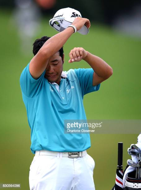 Hideki Matsuyama wipes his brow after hitting a shot from a sand trap along the 16th green and sinking a putt during the second round of the PGA...
