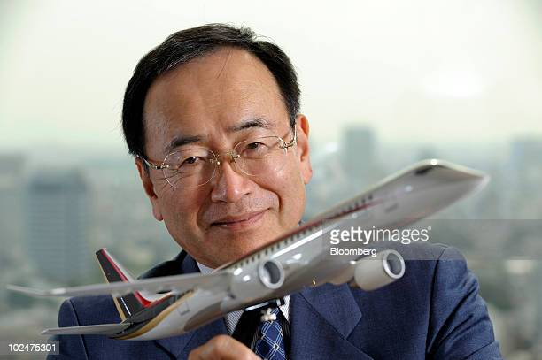 Hideo Egawa president of Mitsubishi Aircraft Corp poses with a model of the company's Mitsubishi Regional Jet during an interview in Tokyo Japan on...