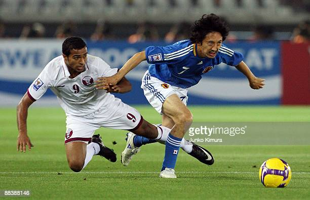 Hideo Hashimoto of Japan and Ali Hassan Yahya Afif of Qatar compete for the ball during the 2010 FIFA World Cup qualifier match between Japan and...