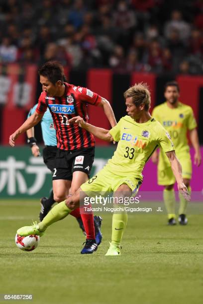 Hidetaka Kanazono of Consadole Sapporo and Tsukasa Shiotani of Sanfrecce Hiroshima compete for the ball during the JLeague J1 match between Consadole...