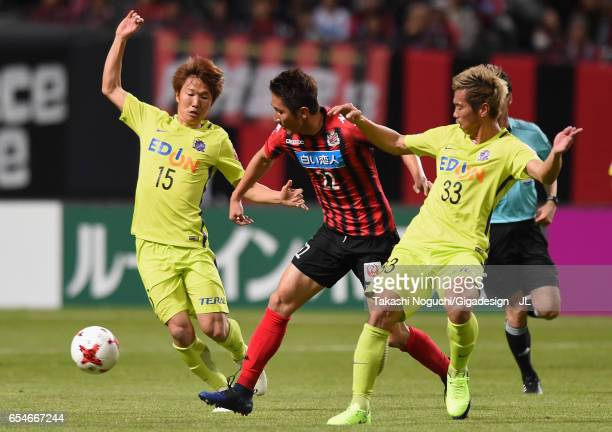 Hidetaka Kanazono of Consadole Sapporo competes for the ball against Sho Inagaki and Tsukasa Shiotani of Sanfrecce Hiroshima during the JLeague J1...