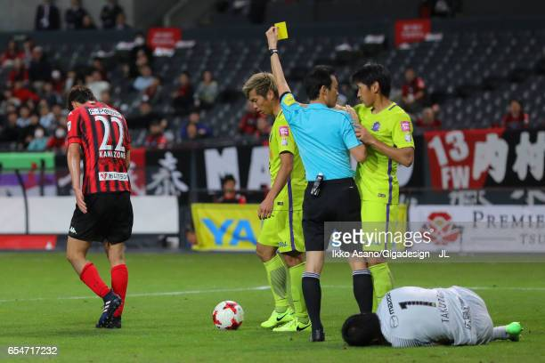 Hidetaka Kanazono of Consadole Sapporo is shown a yellow card by referee Hiroyuki Kimura during the JLeague J1 match between Consadole Sapporo and...