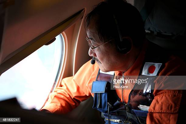 Hidetaka Sato of the Japan Coast Guard keeps watch for debris on board the Japan Coast Guard Gulfstream V aircraft whilst in the search zone for...