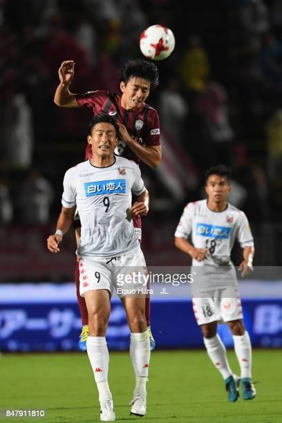 Hideto Takahashi of Vissel Kobe outjumps Ken Tokura of Consadole Sapporo during the JLeague J1 match between Vissel Kobe and Consadole Sapporo at...