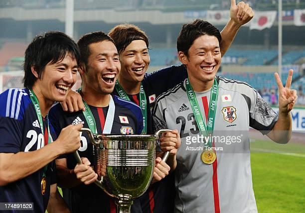 Hideto Takahashi, Yuhei Tokunaga, Masato Morishige and Shuichi Gonda of Japan celebrate with the trophy after winning the EAFF East Asian Cup 2013 at...