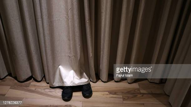 hiding behind the curtain - hiding stock pictures, royalty-free photos & images