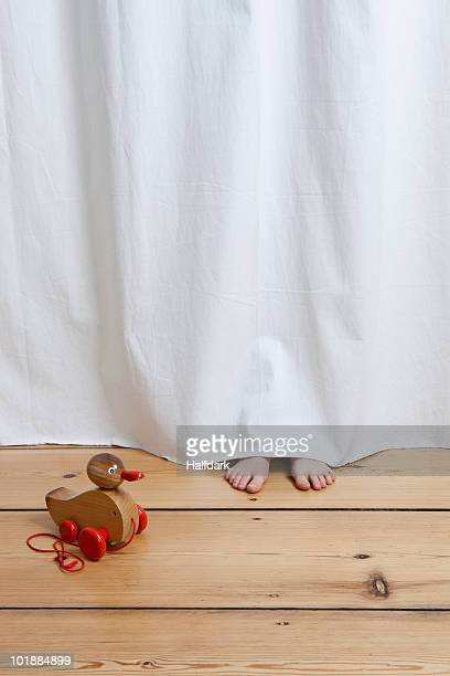 A hiding child's feet sticking out from under a hanging sheet