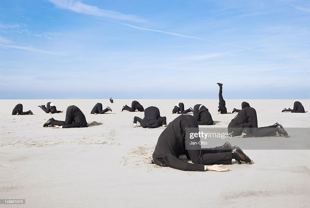 Hiding head in sand : Stock Photo