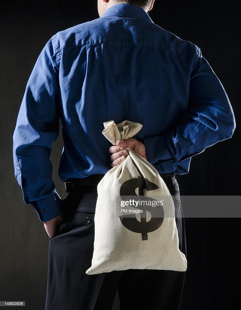 Hiding money behind the back : Stock Photo
