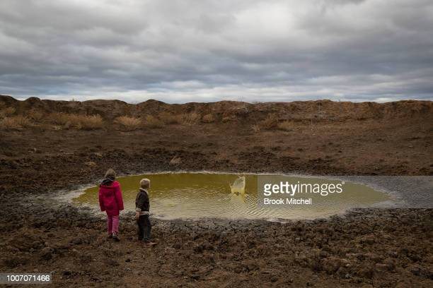 Hiedi 7 and Harry Taylor play in one of the many empty dams on their family farm The Central Western region of New South Wales Australia farmers...