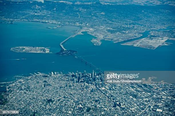 high altitude high contrast san francisco downtown and bay bridge looking towards alameda and the foothills beyond 2 - oakland california skyline stock pictures, royalty-free photos & images
