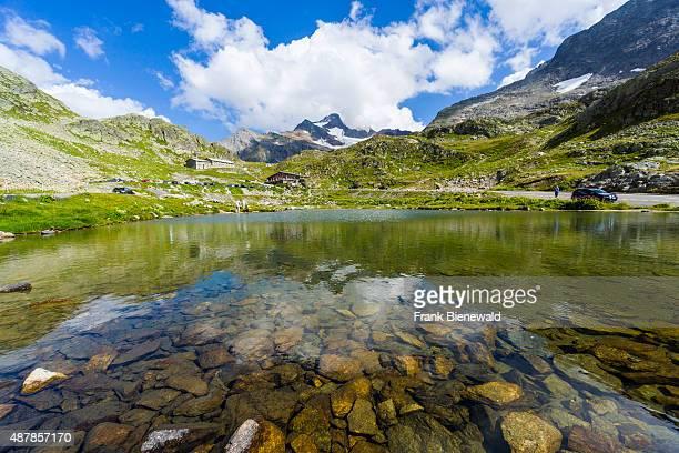 WASSEN GRAUBUENDEN SWITZERLAND High altitude landscape with mountains green meadows and a lake at Sustenpass