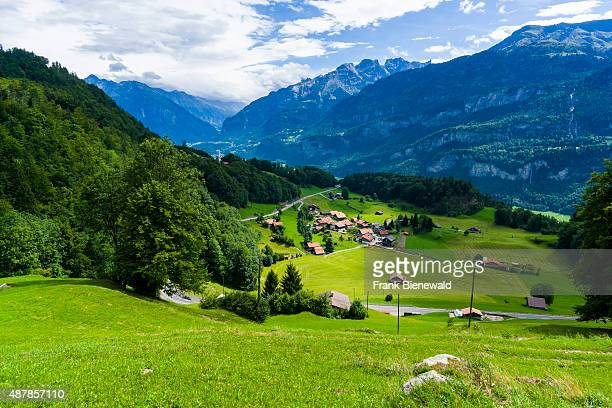 BRUENIGEN BERN SWITZERLAND High altitude landscape with some farmers houses mountains and green meadows at the bottom of Bruenigpass