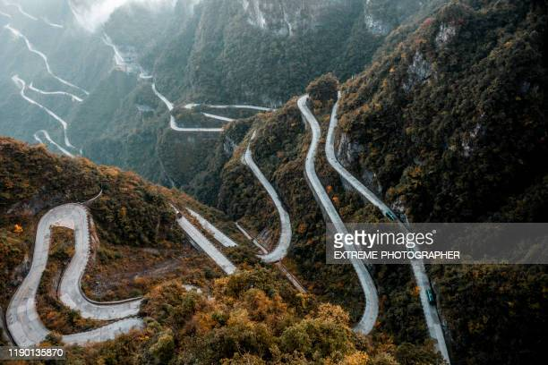 high altitude view of a long slithering curvy mountain road of zhangjiajie (张家界), on tianmen mountain (天门山) - tianmen stock pictures, royalty-free photos & images