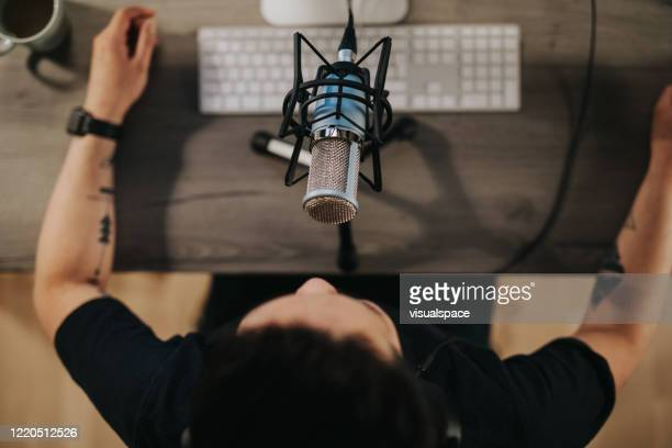 high angel view of a podcaster behind microphone - sound recording equipment stock pictures, royalty-free photos & images
