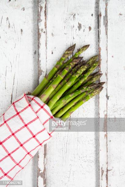 high angel view of green asparagus bunch on wooden table - asparagus stock pictures, royalty-free photos & images