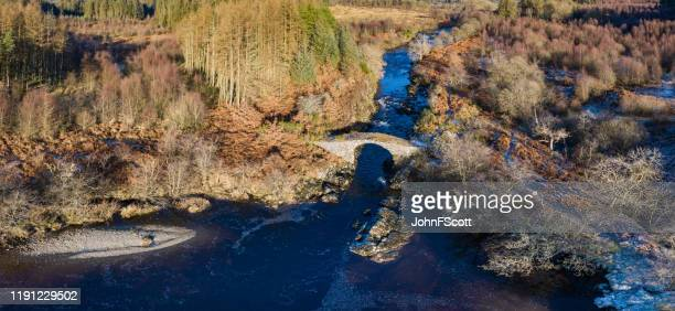 high angle aerial view of an old packhorse bridge crossing a  river running through an area of forest. - dumfries and galloway stock pictures, royalty-free photos & images