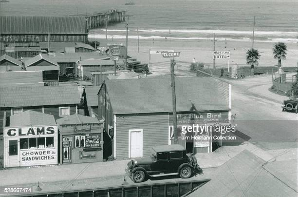 High angle black and white photograph of buildings near Pismo Beach including Clam Stand Smoke Shop Coca Cola ad and car parked on street Beach in...