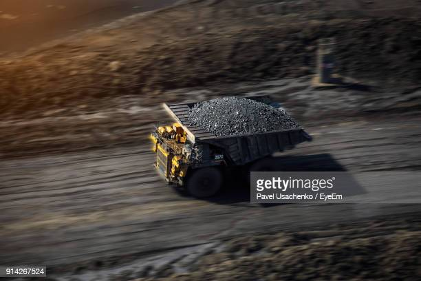 high angle blurred motion of truck with coals moving on road - coal mining stock photos and pictures