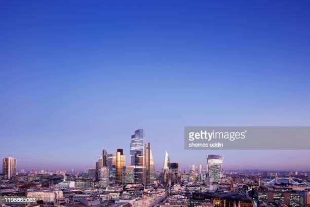high angle cityscape of london illuminated at dusk - aerial view stock pictures, royalty-free photos & images
