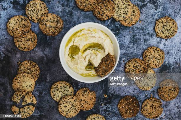 high angle close up of a bowl of hummus and freshly baked seeded crackers. - hartig voedsel stockfoto's en -beelden