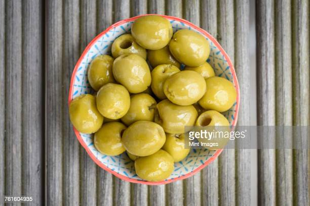 high angle close up of bowl of green olives. - aceitunas fotografías e imágenes de stock